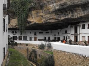 Het kleine witgewassen dorp dat gebouwd is tegen de rotsen langs de rivier